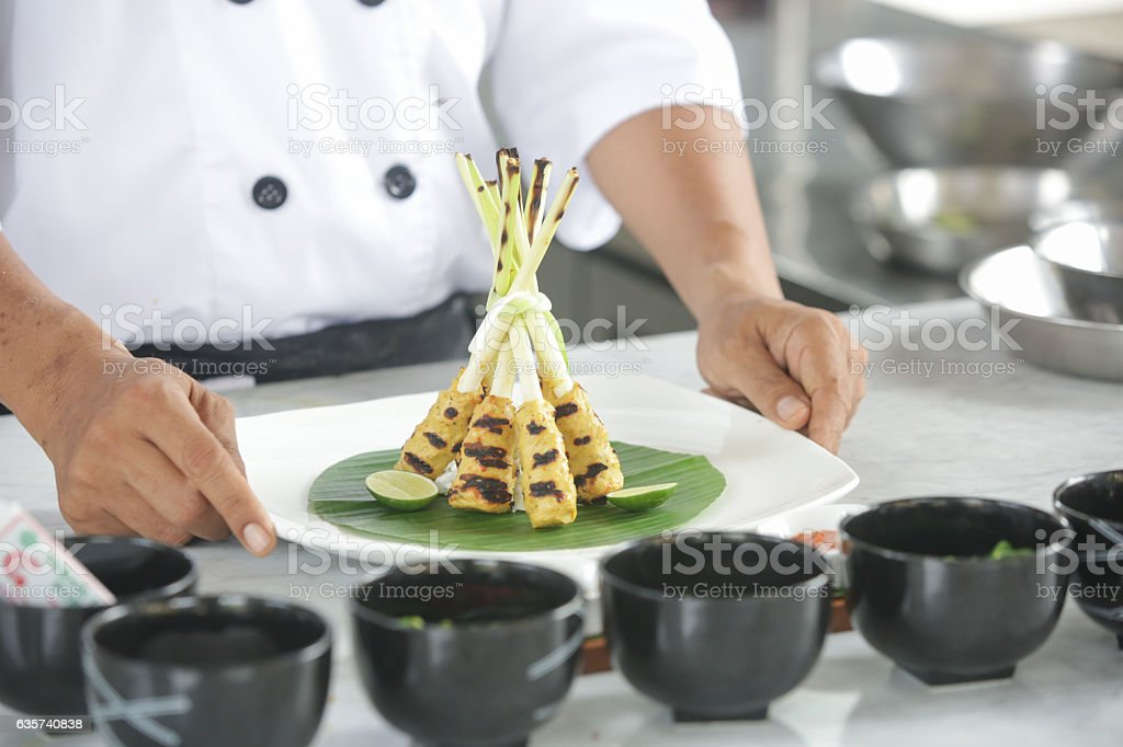 Chef holding a plate of just finished meal stock photo