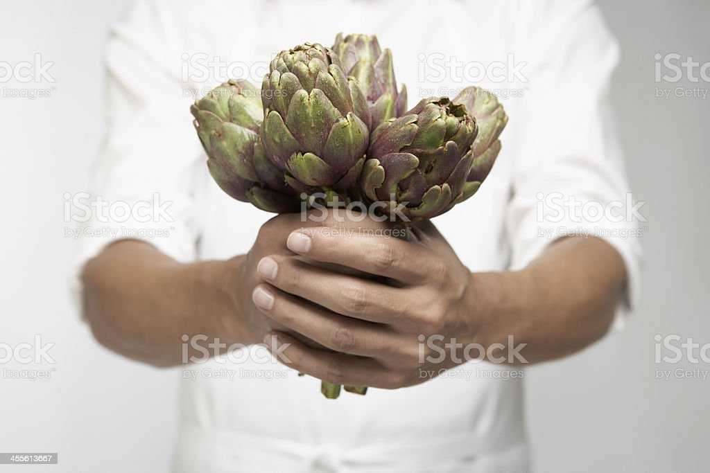 Chef holding artichokes (mid section) royalty-free stock photo