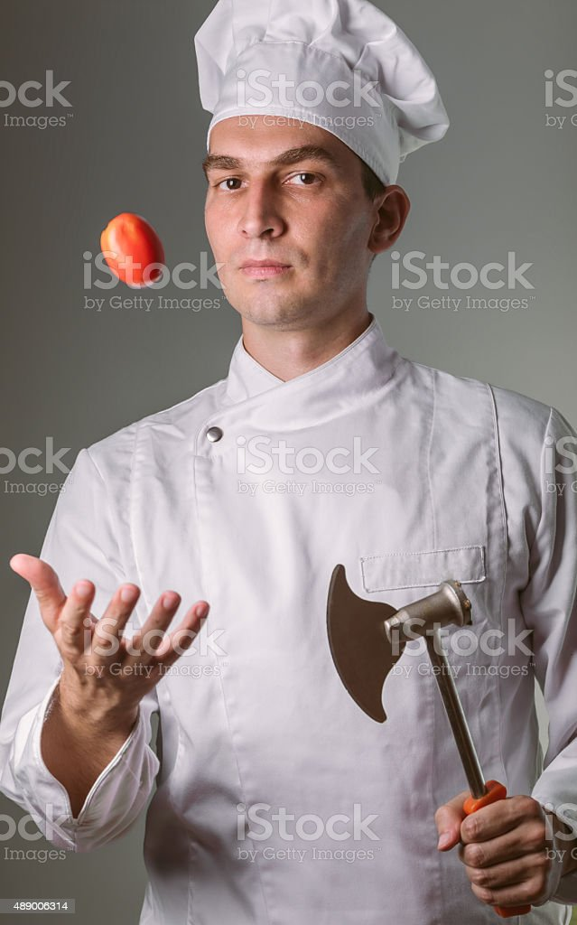 Chef holding chopper and catching tomato stock photo