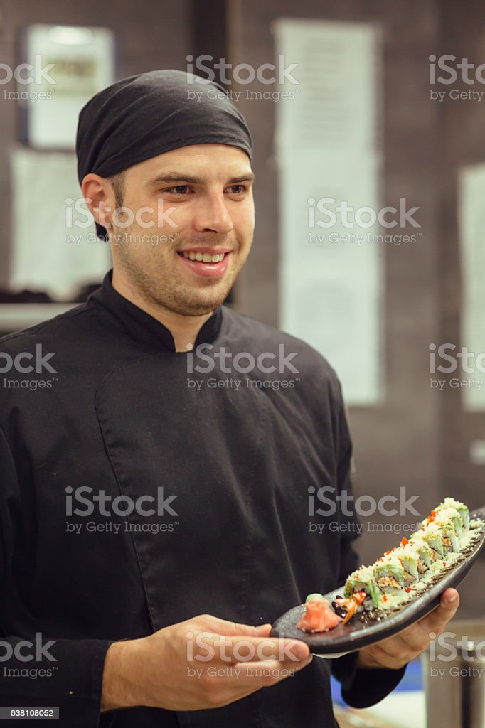 Chef Holding Plate With Dragon Maki Sushi. stock photo