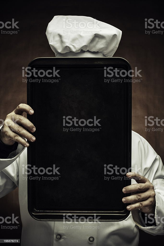 A chef holding up a baking tin stock photo