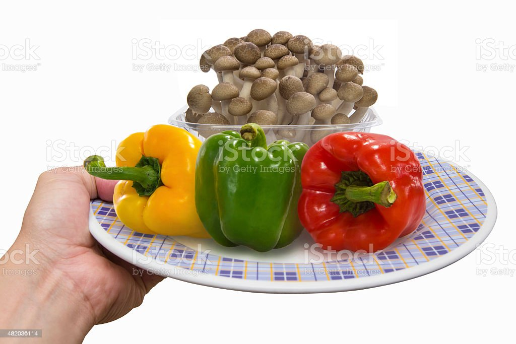 Chef holds empty  white plate with color peppers and mushroom stock photo