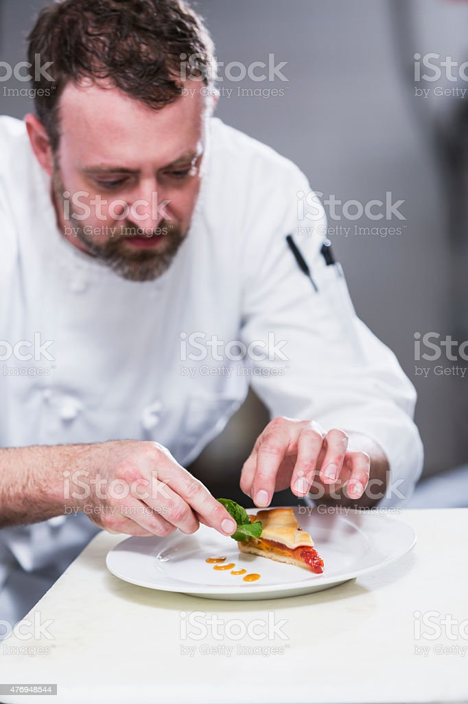 Chef in a restaurant plating food stock photo