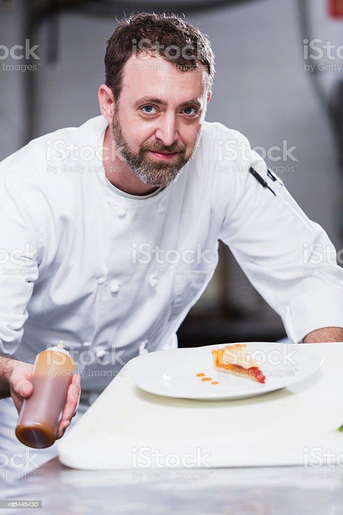 Chef in a restaurant preparing dessert plate stock photo