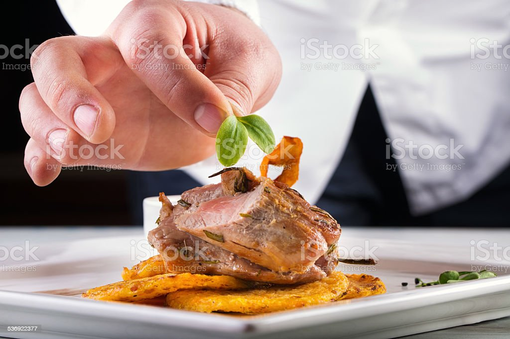 Chef in hotel or restaurant kitchen cooking, only hands. stock photo