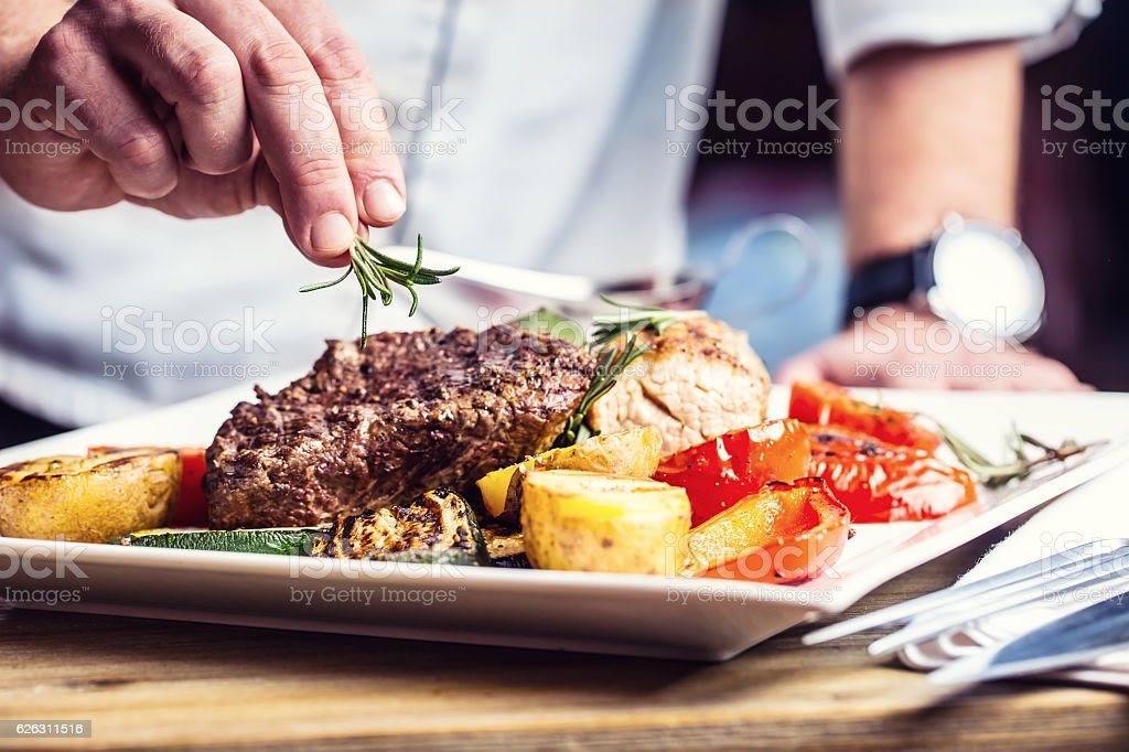 Chef in hotel or restaurant kitchen cooking only hands. stock photo