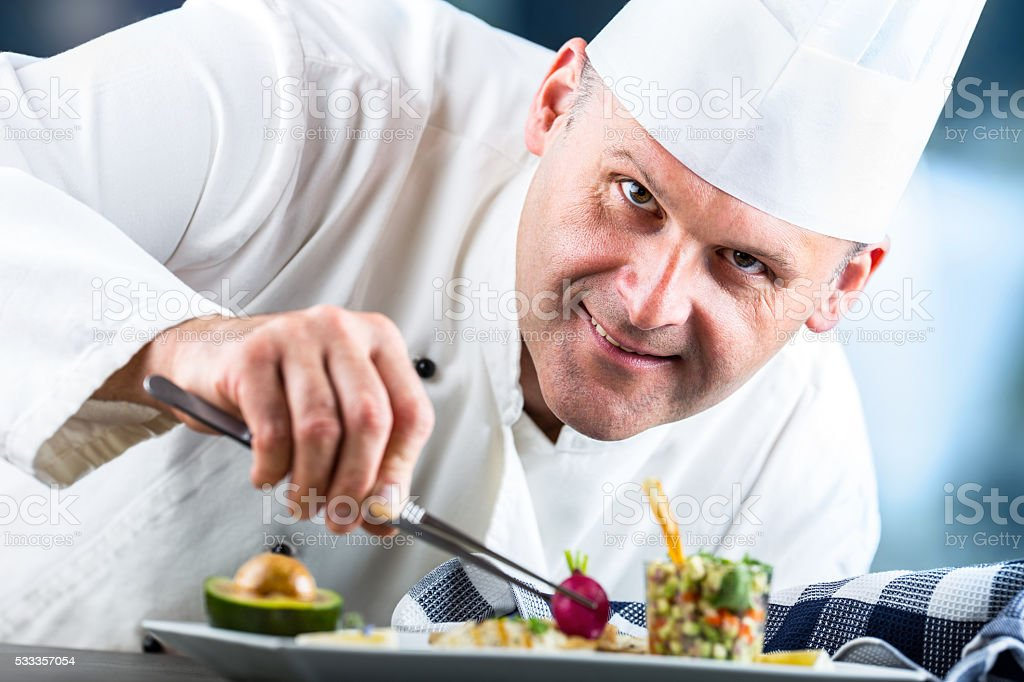 Chef in hotel or restaurant kitchen decorating dish with tweezers. stock photo