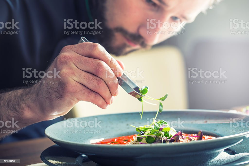 Chef in hotel restaurant kitchen cooking, only hands.Preparing tomato soup stock photo