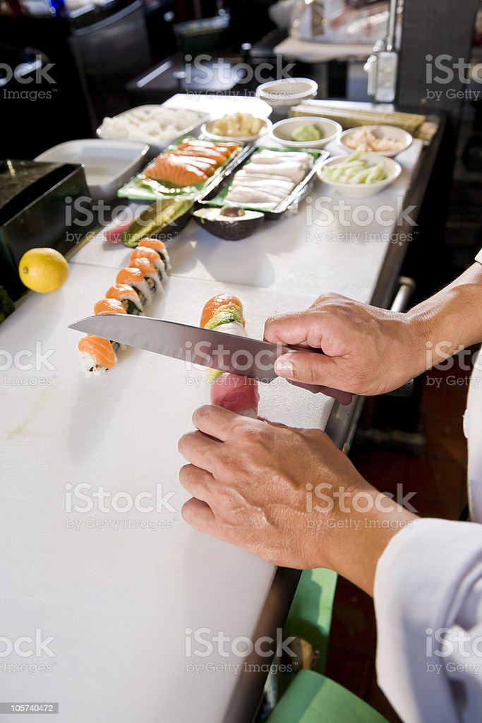 Chef in Japanese restaurant preparing sushi rolls royalty-free stock photo