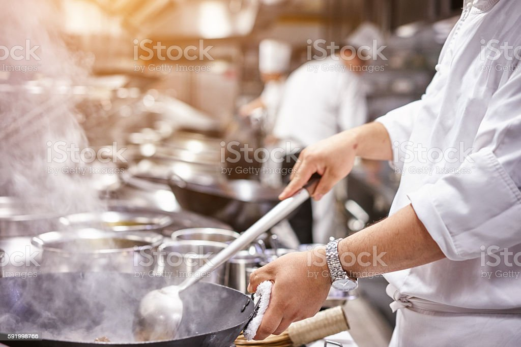 Chef in restaurant kitchen at stove with pan stock photo