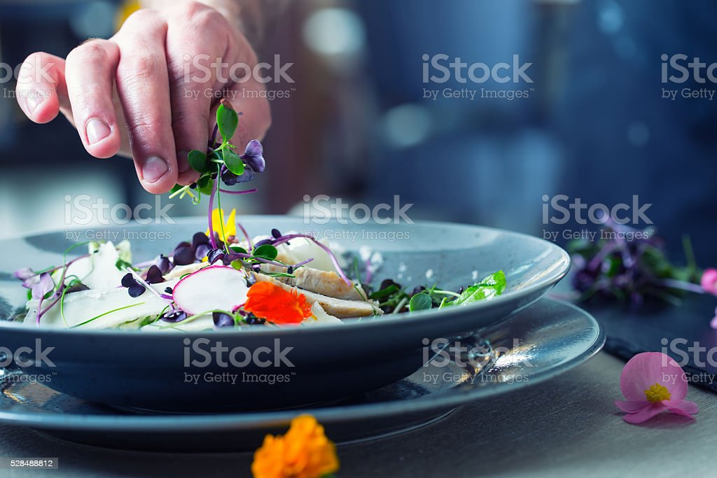 Chef in restaurant kitchen cooking. Preparing vegetable salad stock photo