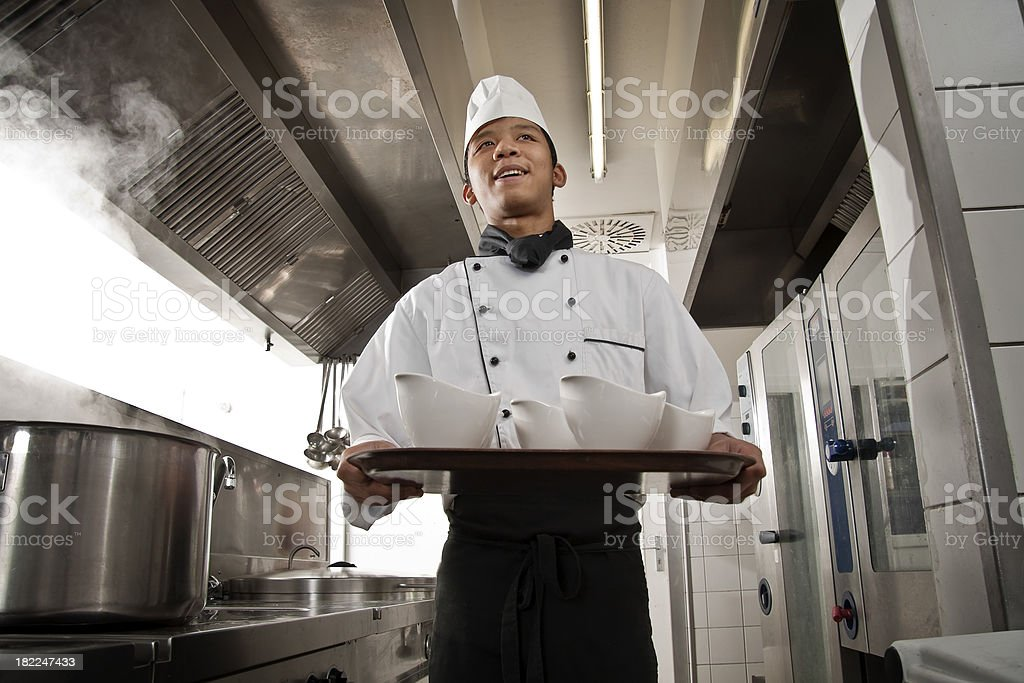 Chef in white chef's coat carrying a pan with bowls. stock photo