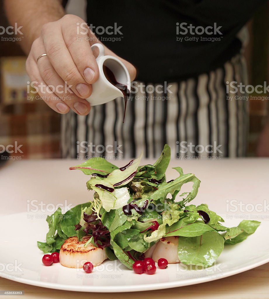 Chef is cooking appetizer with scallops royalty-free stock photo
