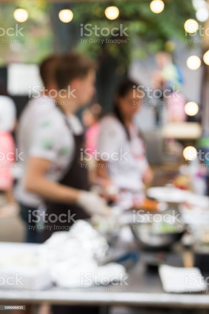 chef is cooking on the street food event. Blurred photo stock photo