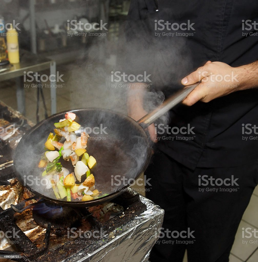 Chef is cooking seafood dish stock photo