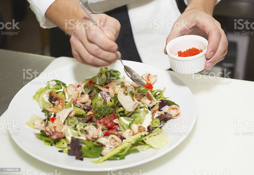 Chef is decorating appetizer dish with flying fish roe royalty-free stock photo