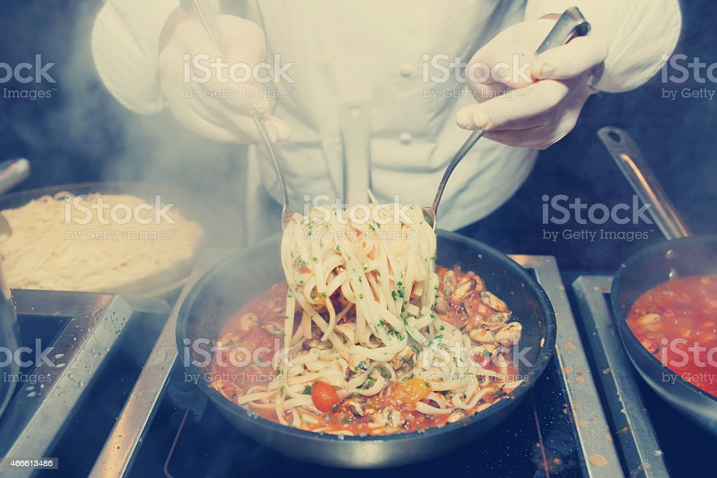 Chef is frying mussels, toned stock photo