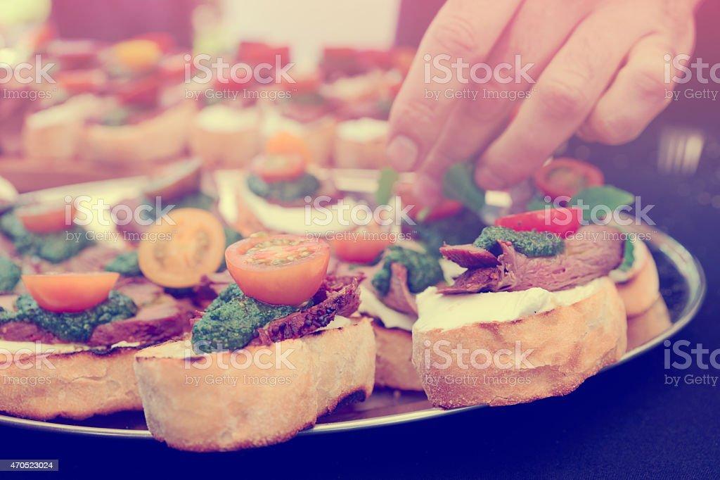 Chef is making bruschettas, toned stock photo
