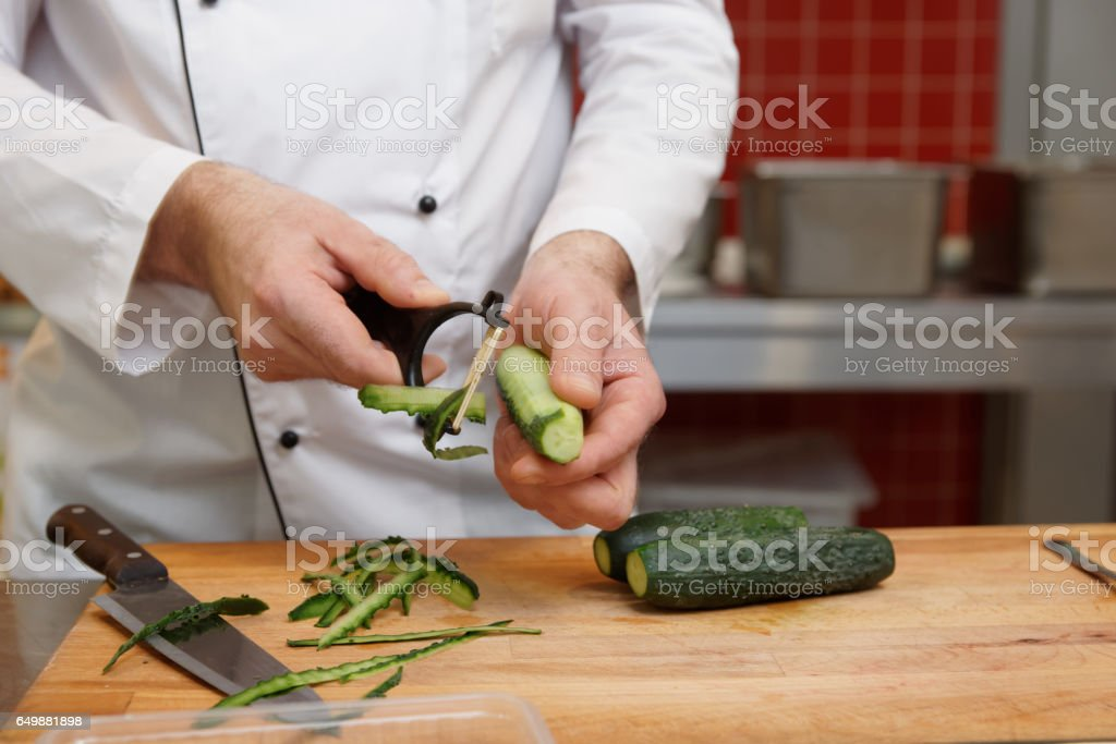 Chef is peeling cucumbers stock photo