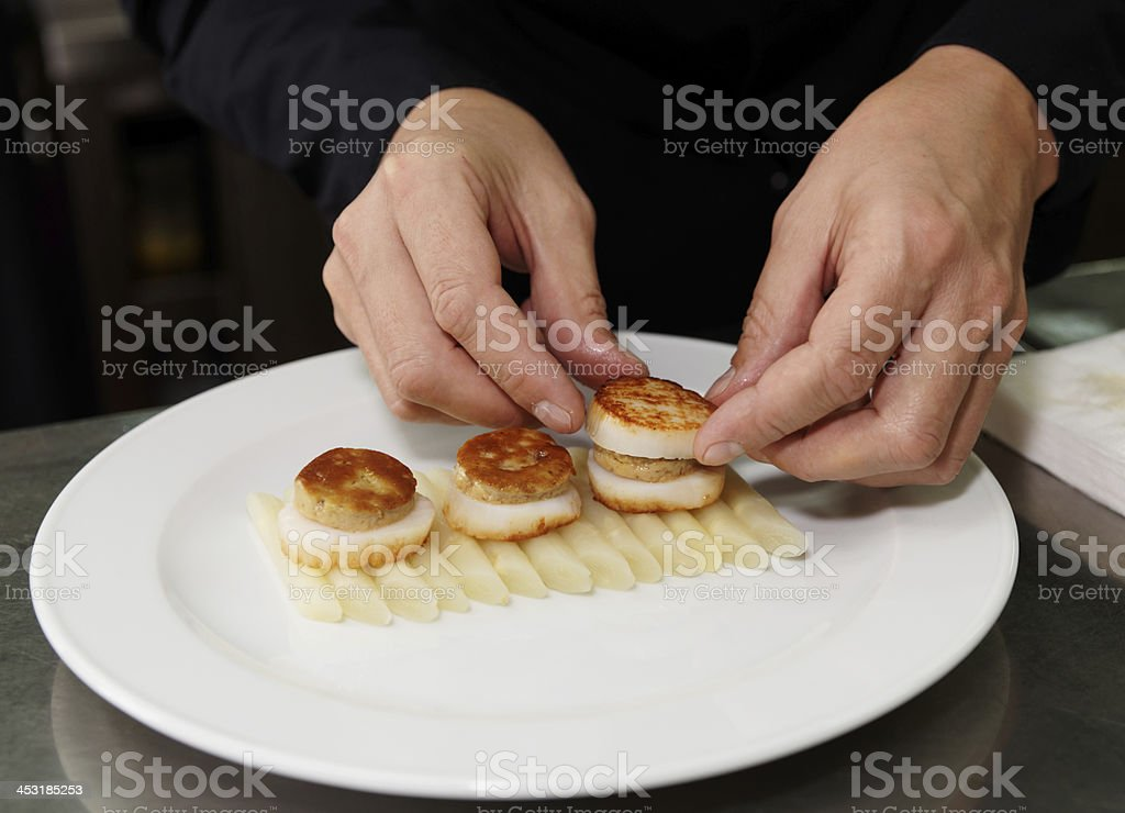 Chef is serving foie gras with grilled scallops royalty-free stock photo