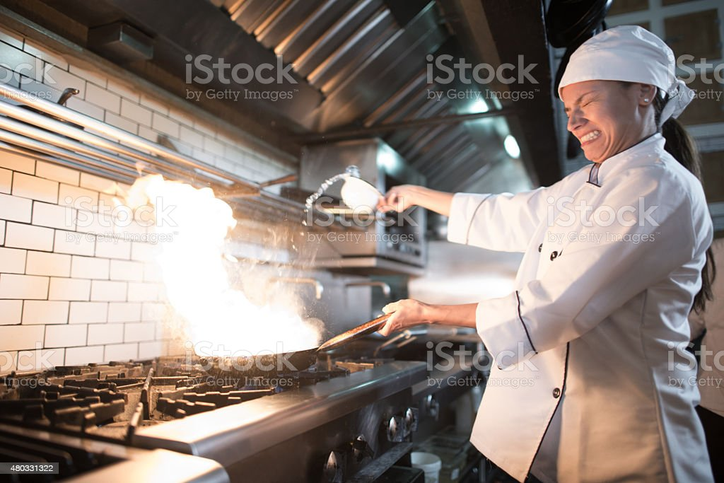 Chef looking scared while cooking a stir fry stock photo