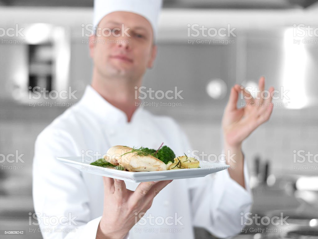 Chef offering chicken dish stock photo