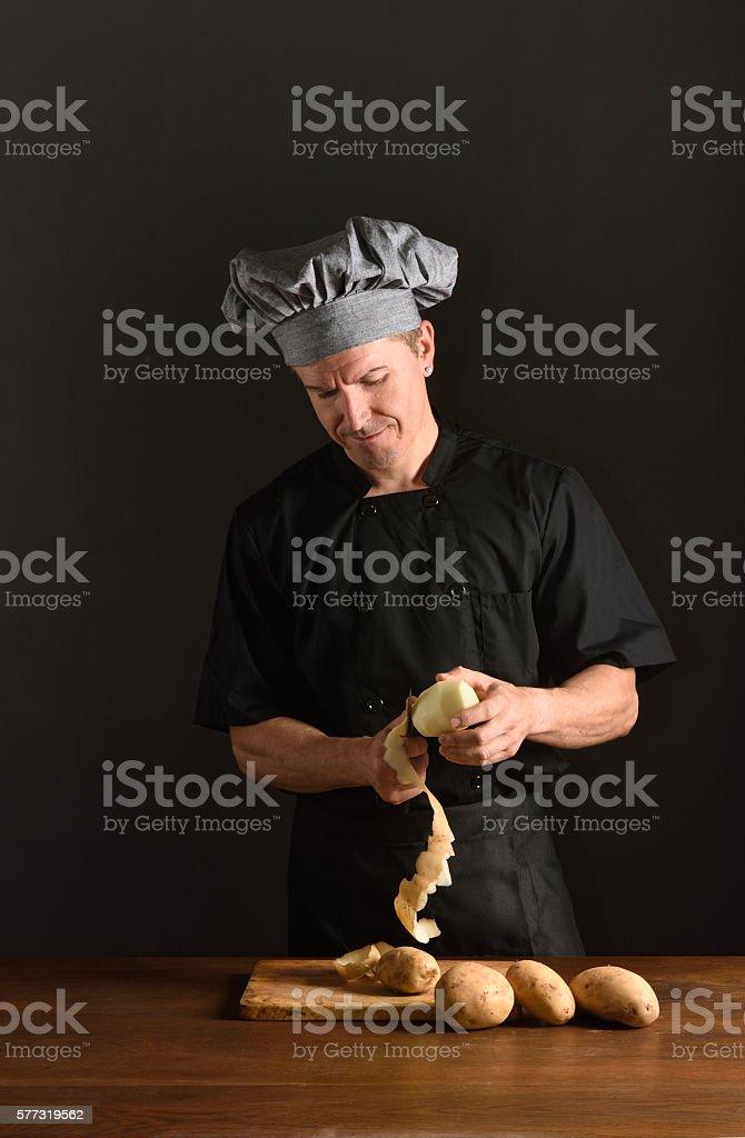 chef peeling potatoes stock photo