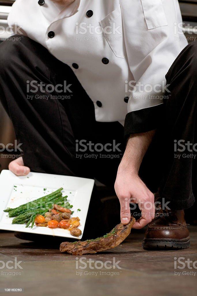 Chef Picking Steak Off Floor stock photo