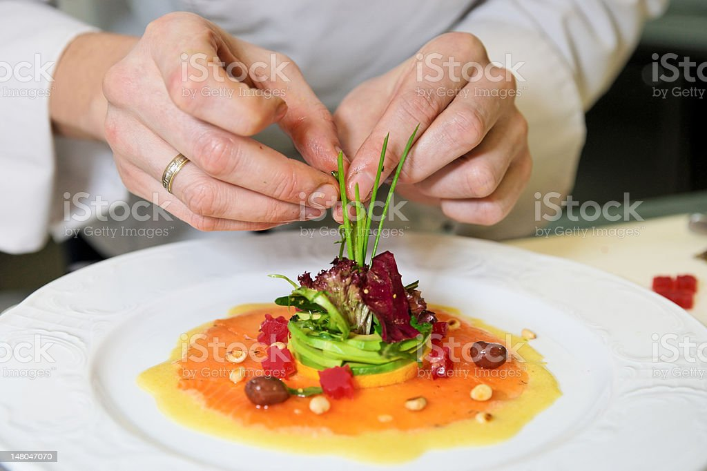 Chef placing decorating details on an appetizer stock photo