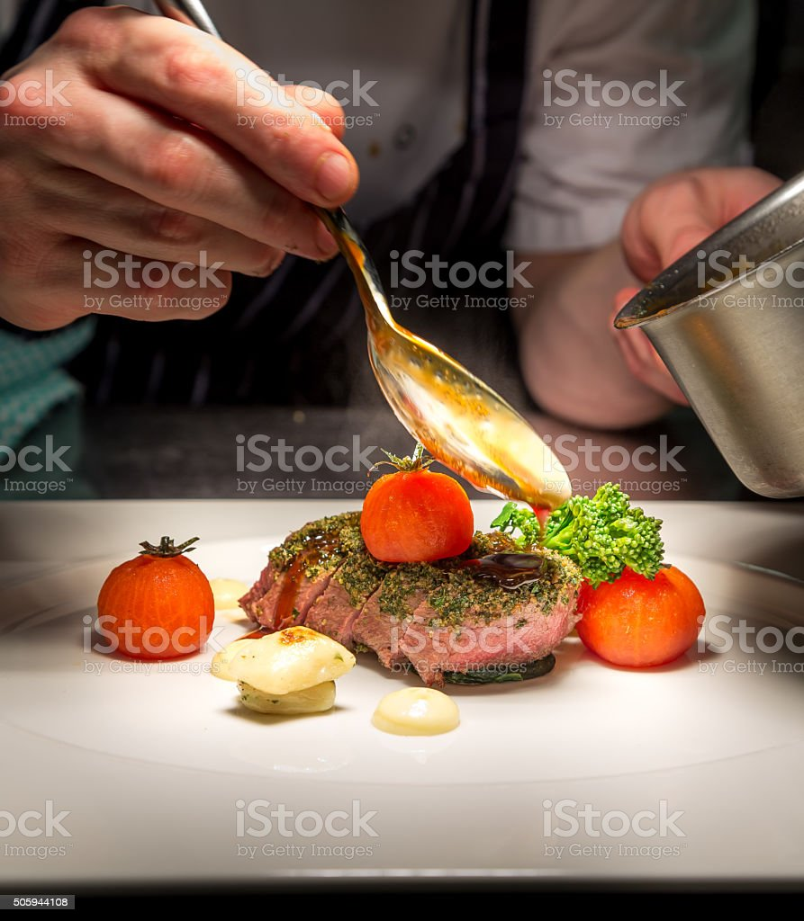 Chef plating Tender Lamb with herb crust, cherry tom,Jus stock photo