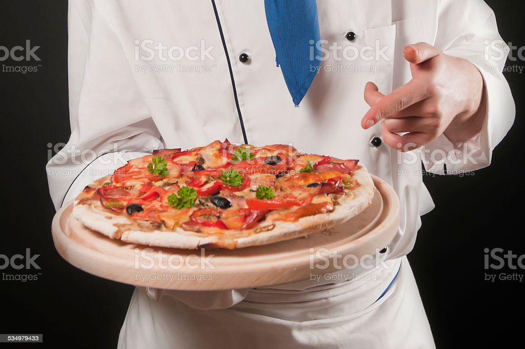 Chef pointing on a pizza stock photo