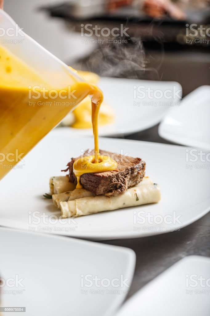 Chef pouring gamy sauce stock photo