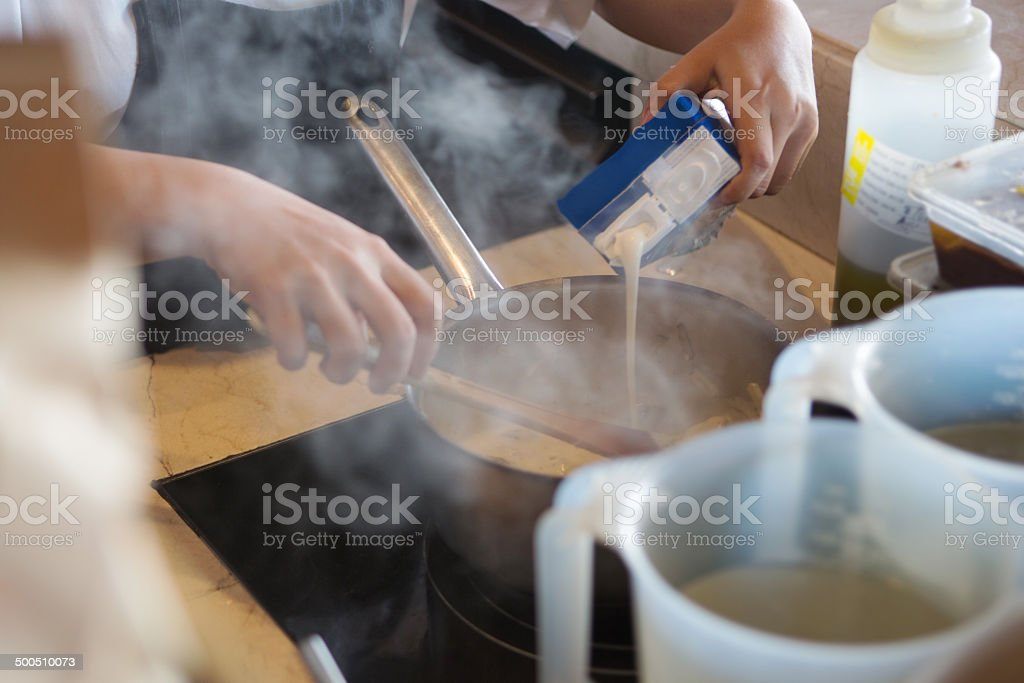 Chef pouring milk in a dish stock photo