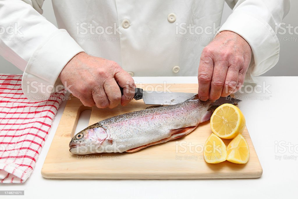 chef prepares to fillet rainbow trout fish with lemon royalty-free stock photo