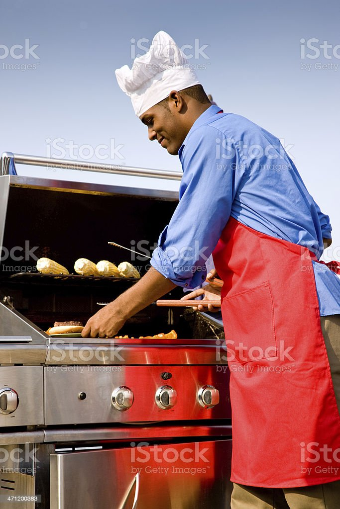 BBQ Chef preparing Burgers and Corn royalty-free stock photo