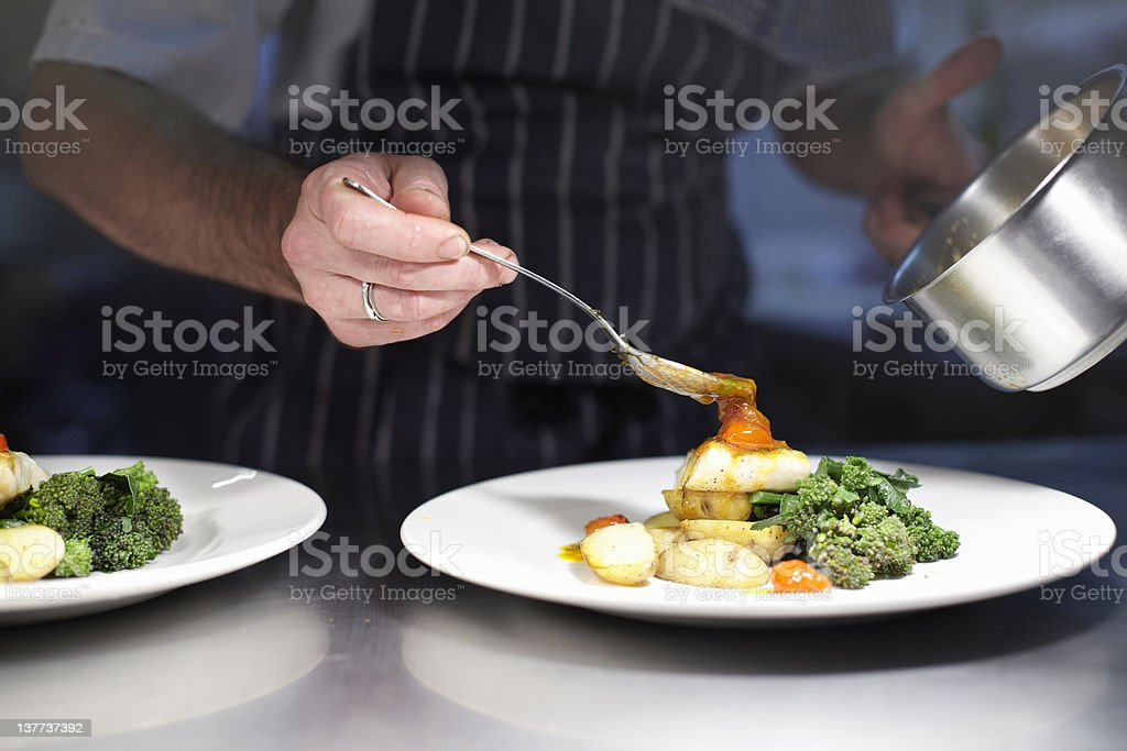 Chef preparing dish in kitchen stock photo