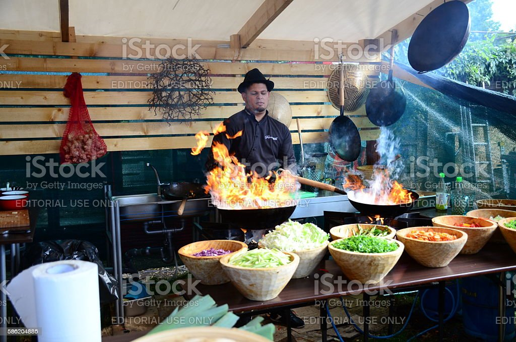 Chef preparing food and flames leaping from a wok. stock photo