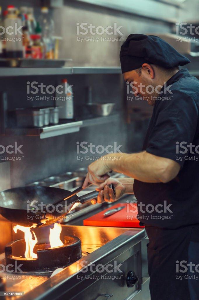 Chef preparing food in wok stock photo