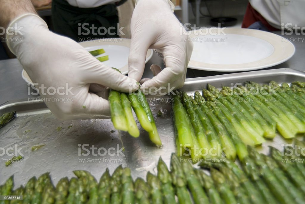 A chef preparing two rows of asparagus in a pan royalty-free stock photo