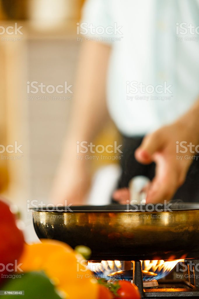 Chef reaching for frying pan stock photo