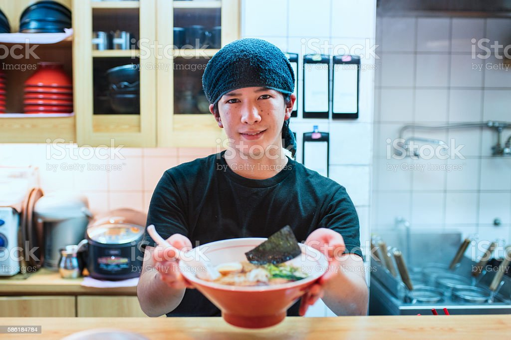 Chef serving a bowl of freshly made ramen stock photo
