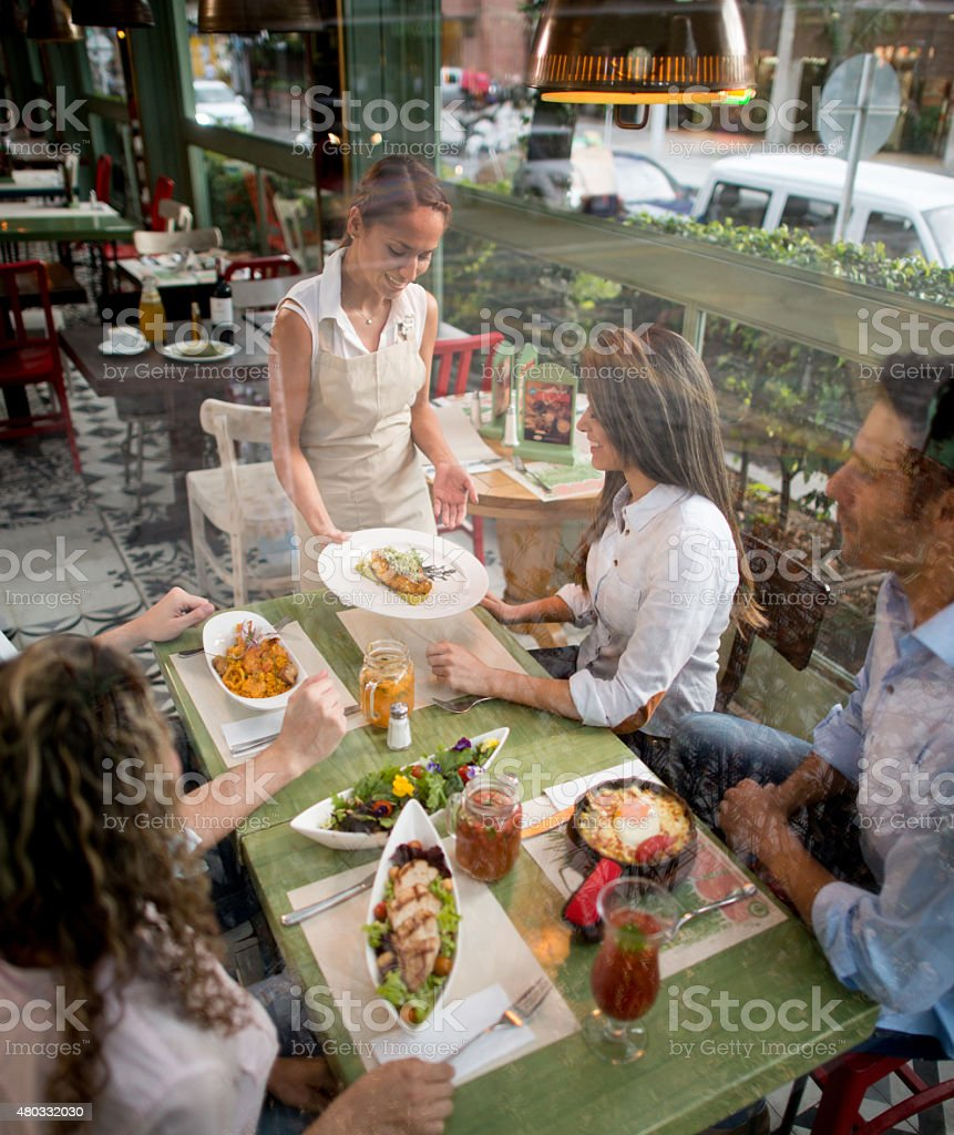 Chef serving plates to a group of friends stock photo