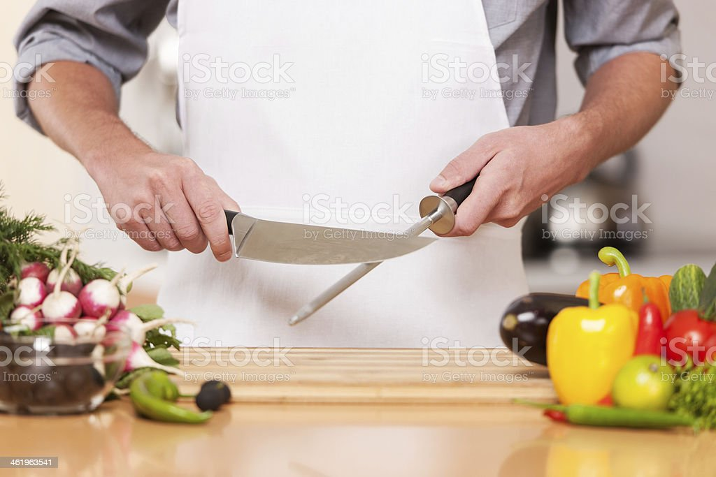 A chef sharpening a knife in his kitchen  stock photo