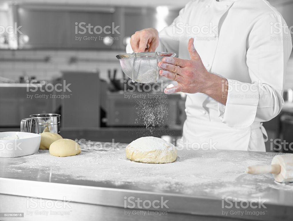 Chef sifting flour over a ball of dough stock photo