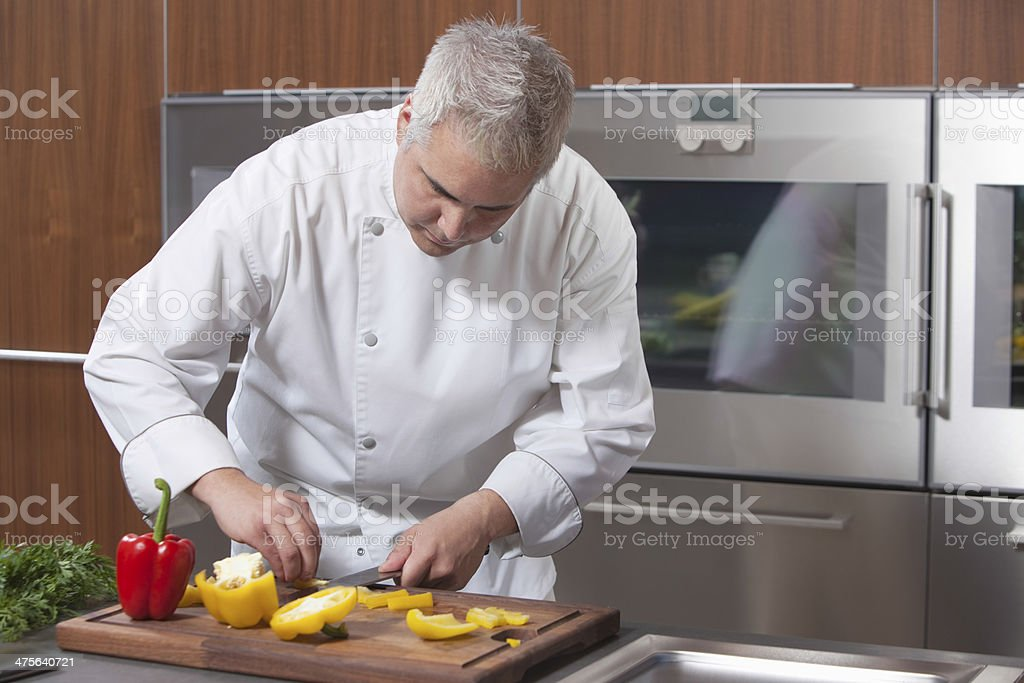 Chef Slicing Bell Pepper In Commercial Kitchen royalty-free stock photo