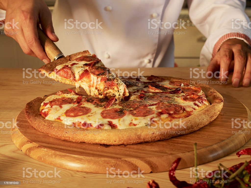 Chef slicing pizza. royalty-free stock photo
