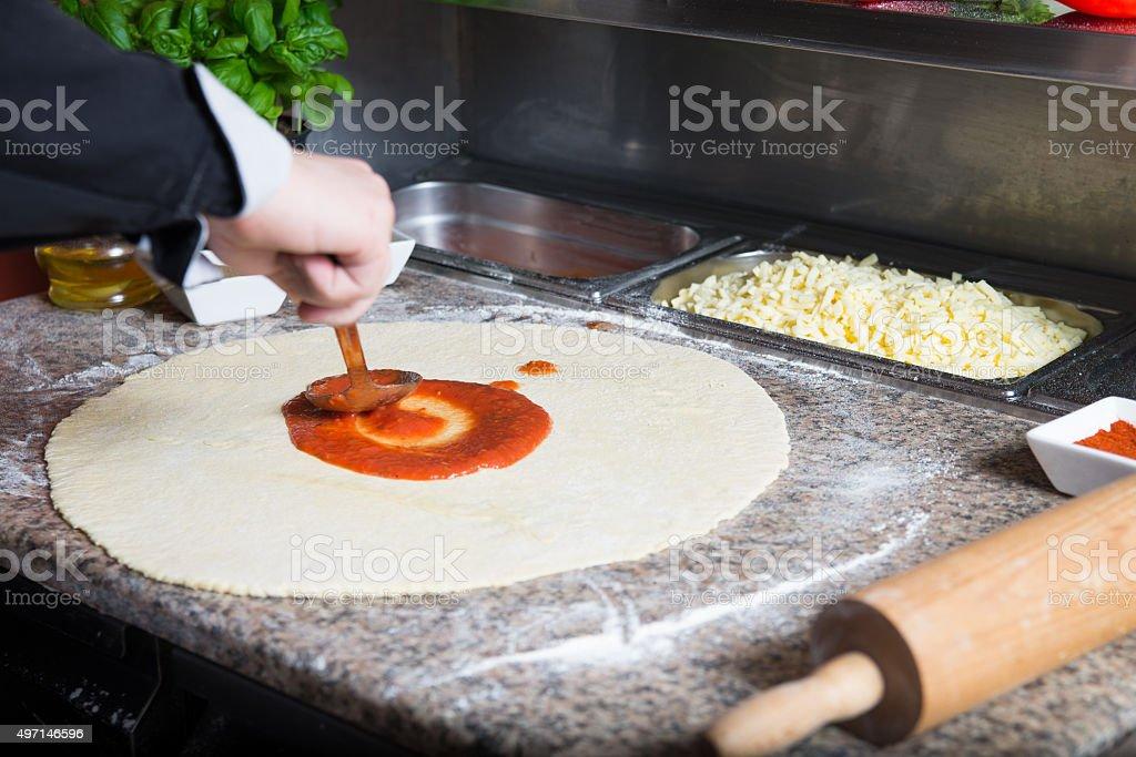 Chef smear pizza dough with tomato sauce. stock photo