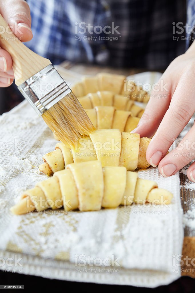 Chef smearing raw croissants with brush in yolk stock photo