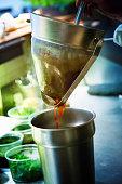 Chef straining sauce in restaurant kitchen