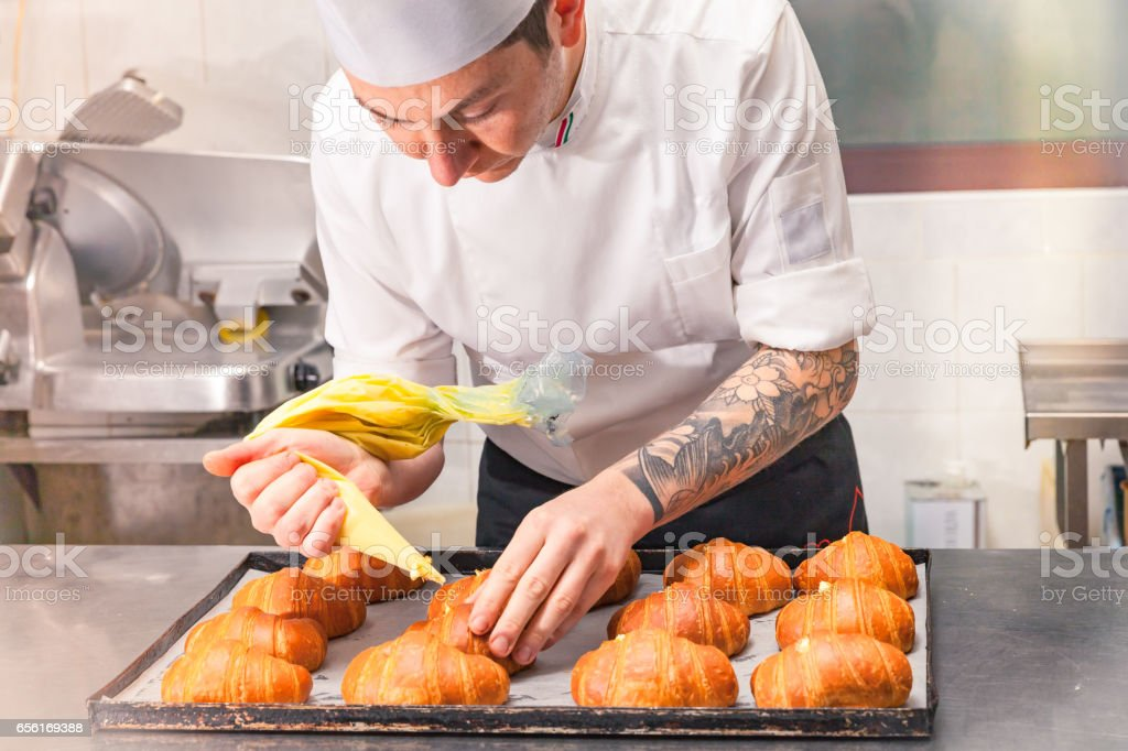 Chef stuffing croissants with custard stock photo